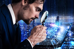 Man looks at the magnifying glass a laptop. Concept of software analysis Royalty Free Stock Photography