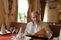 Man looks at menu Stock Image