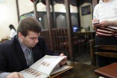 Man looks through menu Royalty Free Stock Photo