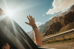 Man looks mountains window car arm outstretched sunlight stock photo