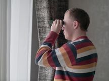 Young man looks out the window through binoculars stock photo