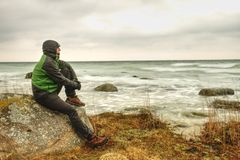 Man looks over the sea bay and enjoy wild nature. A man admires the beauty of nature force royalty free stock image