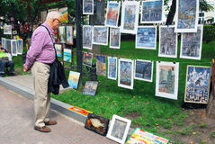 A man looks at paintings shown on Gogol boulevard. Stock Photo