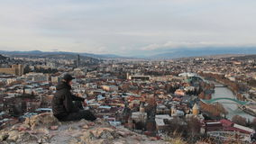 A man looks at the panorama of Tbilisi. A man in black jacket and black cap looks at the panorama of Tbilisi from nearest hill. Beautiful panorama where old Royalty Free Stock Photos