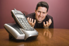 Man looks at the phone frustrated. A man begs for the phone to ring Royalty Free Stock Image