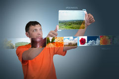 Man looks at photos of the virtual display Royalty Free Stock Photography