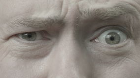 A man looks and raises his eyebrows. A man looks straight, left, right and raises his eyebrows stock footage