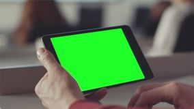Man looks at the screen of the tablet with a green screen. Stock. Chroma key on the screen of the tablet in the hands.  stock video footage