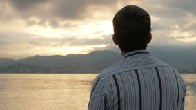 The man looks in a shirt looking at the sunrise on the beach of the ocean. The sun rises from behind the mountains. The stock footage