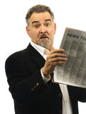 Man looks shocked while reading newspaper Royalty Free Stock Photos