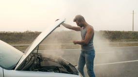 A man looks at a smoking engine of a broken car