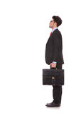 Man looks somewhere up. Side view full length picture of a young business man standing with his suitcase in his hand and looking at something upwards, away from Royalty Free Stock Image