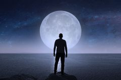 A man looks at the stars and the moon. Elements of this image furnished by NASA royalty free stock photos