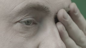A man looks straight and wipes his eyes. A man looks directly and wipes his eye with his hand stock footage