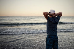 Man looks at the sunset over the sea. Stock Image