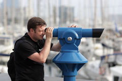 Man looks through telescope Royalty Free Stock Photo