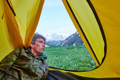 The man looks from tent at mountains Stock Image