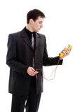 Man looks at the testimony of a multimeter. A young man in a suit, looks at the testimony of a multimeter, isolated on a white background Stock Photos
