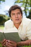 Man looks to the distance while reading a book. As he is lying down in a park Stock Photography