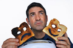 Man looks up and holds two different slices of toast bread Royalty Free Stock Images