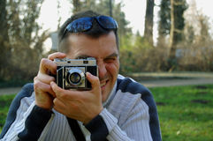 Man looks in vintage camera Royalty Free Stock Photos