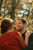 Man looks into woman& x27;s eyes and smiles outdoors in fall Stock Photo