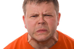 Man Looks At You with Pained Expression. A young man in an orange shirt looks angrily at you Stock Images