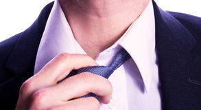 Man loosening tie. Businessman loosens tie in act of relaxation Stock Photos