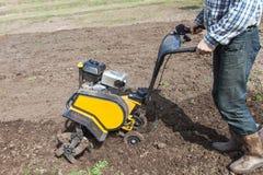 Man loosens the soil cultivator Stock Photos