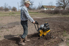 Man loosens the soil cultivator Royalty Free Stock Photo