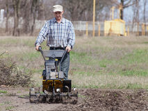Man loosens the soil cultivator Royalty Free Stock Photos