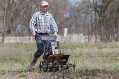 Man loosens the soil cultivator Stock Images