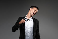 Man loosing tie on grey background. Royalty Free Stock Photography