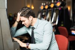 Man losing money in a casino. Unlucky young men looking stressed and feeling sad after losing all his money in a slot machine at a casino Stock Images