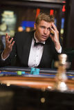 Man losing at roulette table. Man losing roulette table in casino royalty free stock photo