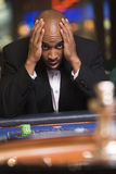 Man losing at roulette table. In casino royalty free stock image