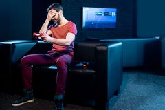 Sad man playing video games with gaming console in the club stock photography