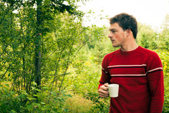Young man in nature with a mug of coffee Stock Photos
