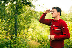 Young man in nature with a mug of coffee Royalty Free Stock Images