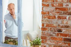 Man lost in thought. Elderly man in sweater lost in thought by the window royalty free stock images