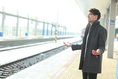 Man lost the train. Handsome young man lost the train standing on railway platform outdoor Royalty Free Stock Images