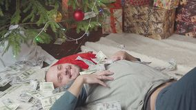 A man is sleeping with a lot of dollars and a Christmas tree. A man with a lot of dollars wakes up after Christmas stock video footage
