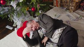 Sleeping man with a lot of dollars and a Christmas tree. A man with a lot of dollars wakes up after Christmas stock video