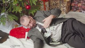 A man is sleeping with a lot of dollars and a Christmas tree. A man with a lot of dollars wakes up after Christmas stock video