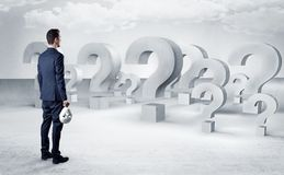 Man with lot of question mark signs and icons. Businessman standing and looking to a bunch of question mark signs royalty free illustration