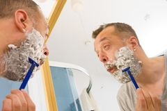 Guy shaving his beard in bathroom royalty free stock photo