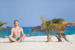 Man in lotus pose. Young man sitting near the palm on the beach in lotus pose Stock Image