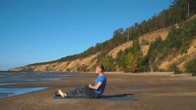 Man in Lotus pose meditating at the beach stock video