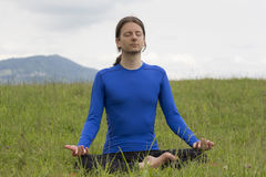 Man in lotus pose meditating during yoga outdoors Stock Photo