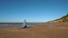 The man in the Lotus position meditating in front of the ocean stock video